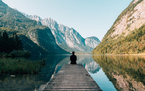 sitting alone by a lake and moutains