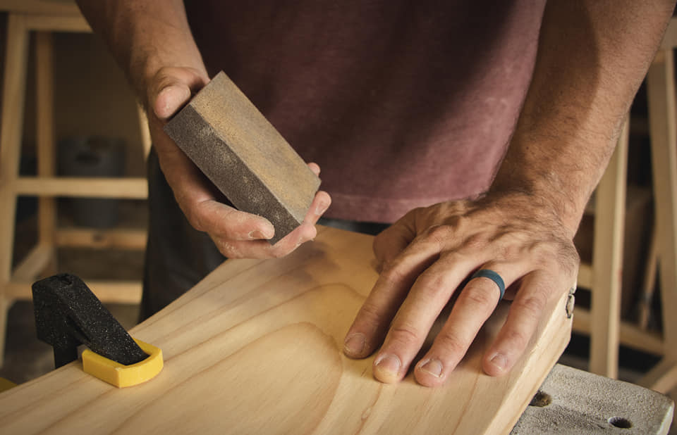 Man working in the garage with wood, sanding a plank with his hand while wearing a blue mens flex silicone wedding ring from orbit rings