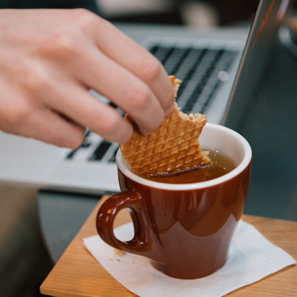 hand dipping stroopwafel into cup of coffee