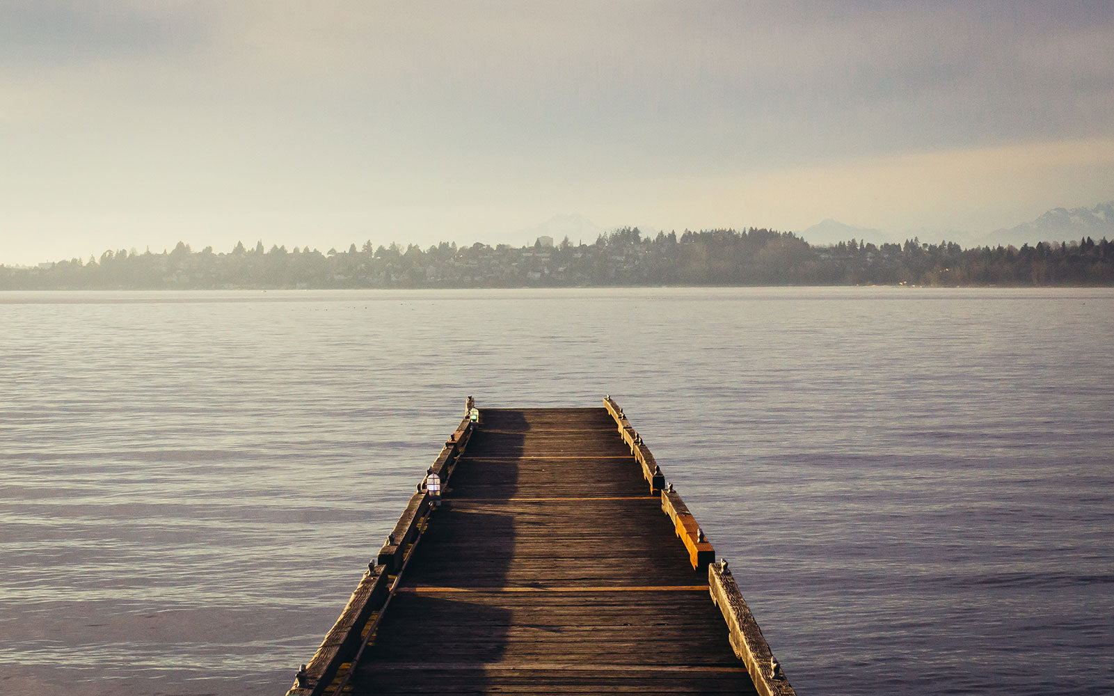 Image of a pier leading to a peaceful lake