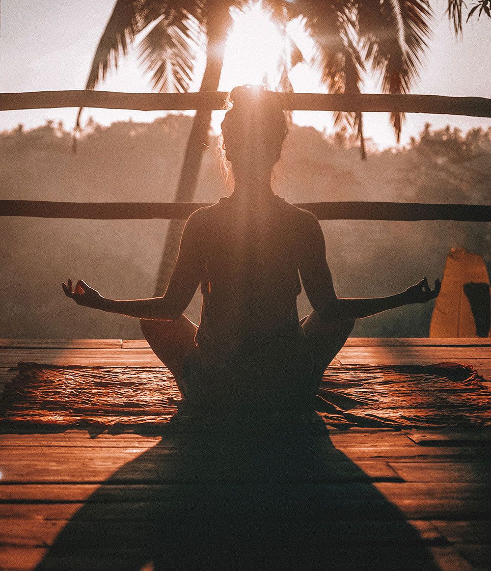 Woman sitting in meditation looking at sunset with palmtree