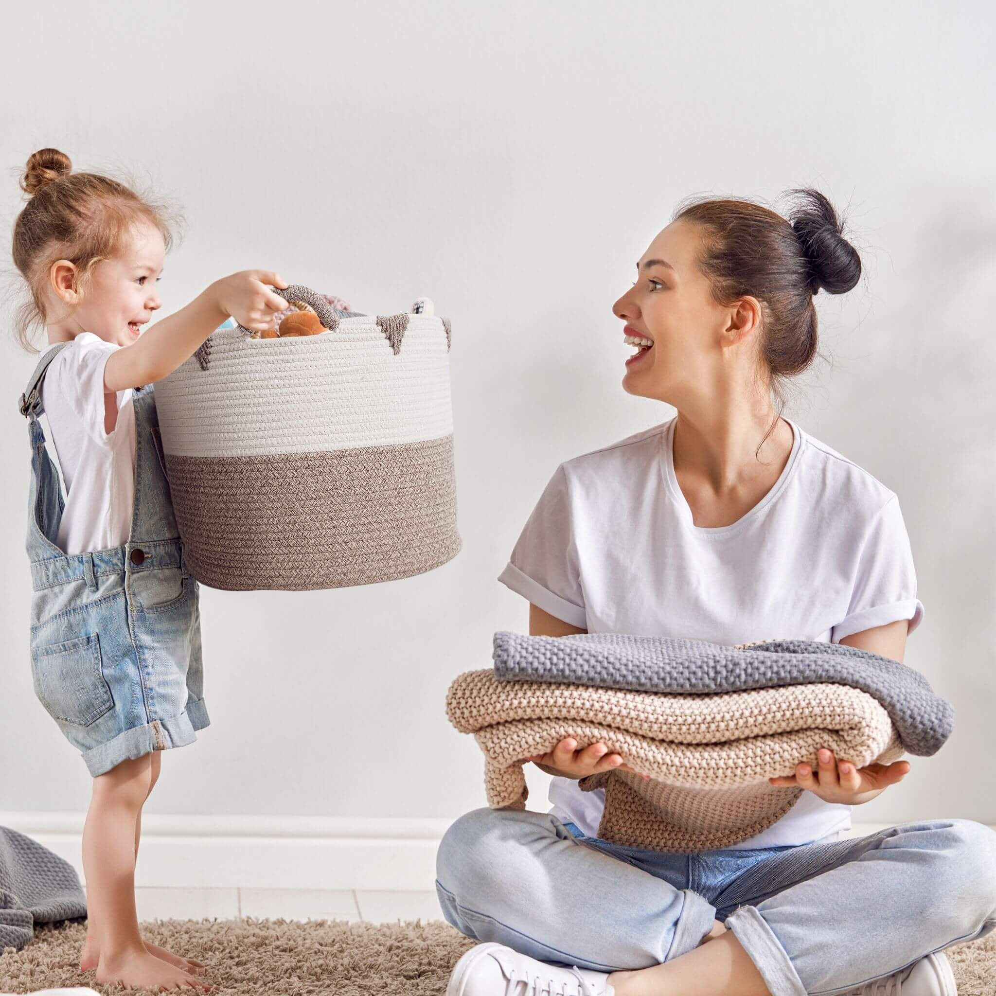 kid playing with a basket storage and mom smiling