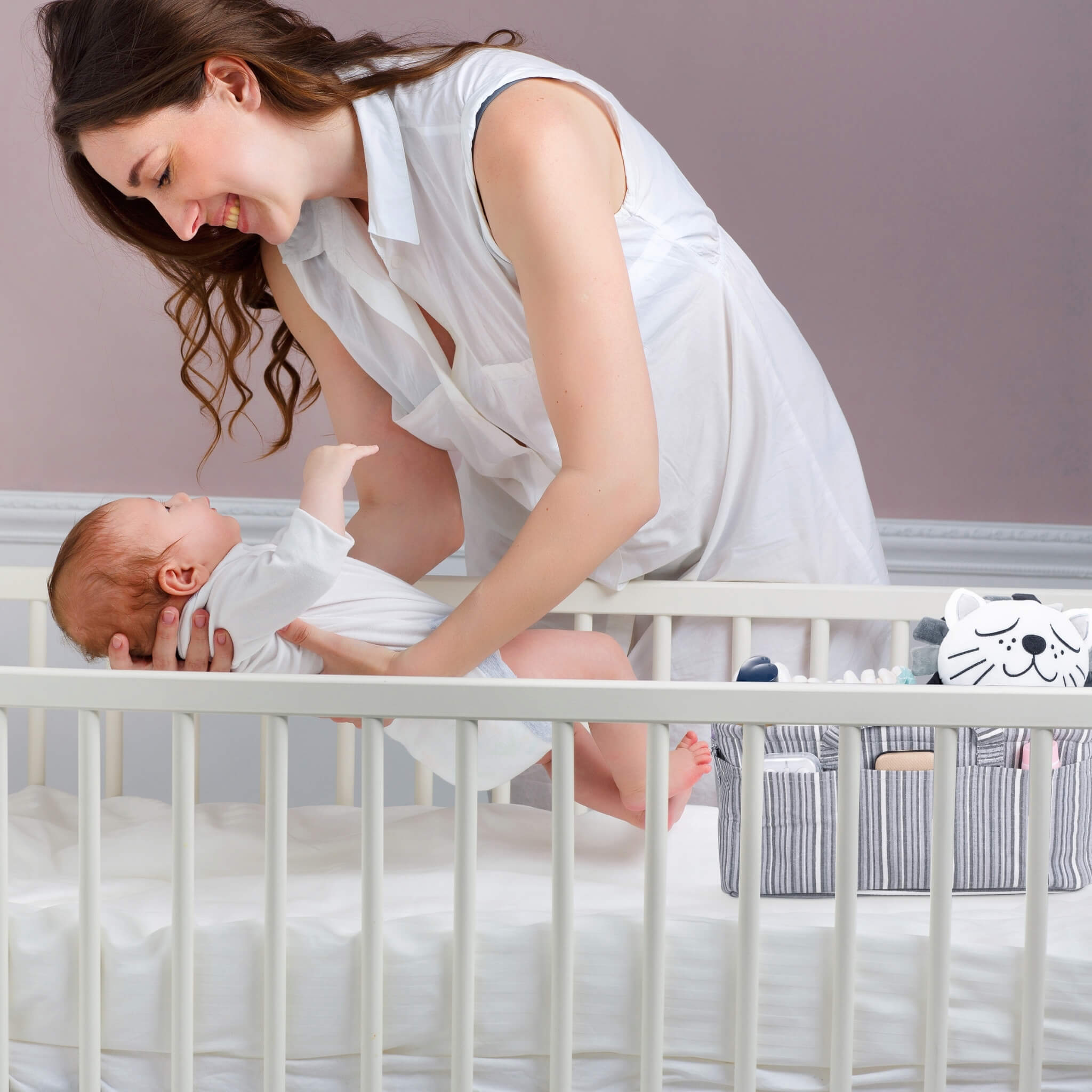 women with baby on hand and a grey caddy for changing table organizer