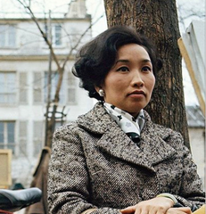 Asian woman seated wearing a black and white wool coat