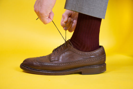 Man wearing burgundy socks in brown leather shoes tying his shoelaces