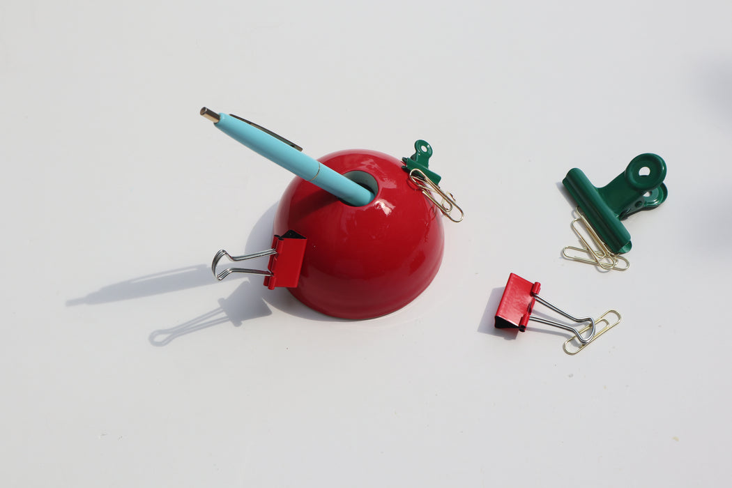 Red Hemisphere Magnetic Ceramic Paperweight with blue pen inside and metal clips scattered around it