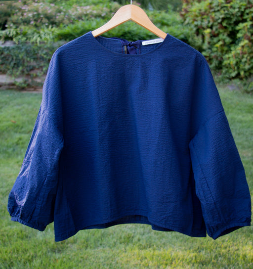 Dark blue popover shirt with grosgrain ribbon tie back closure and striped crinkle