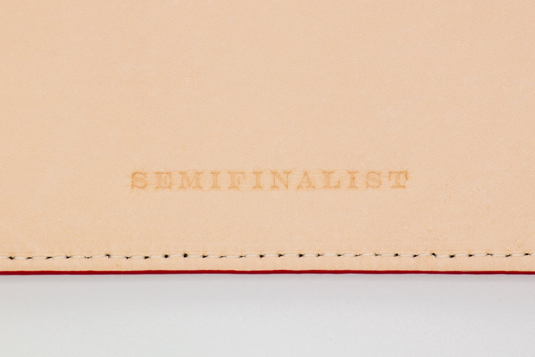 close up of semifinalist logo on Tan and Red leather file folder