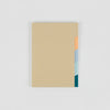 Sand color notebook with yellow, blue and green tabs