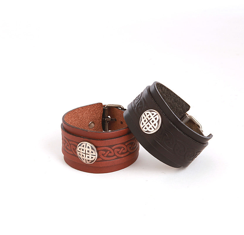 Black and brown leather wrist cuffs with pewter conch and buckle fasteners by Lee River Leather