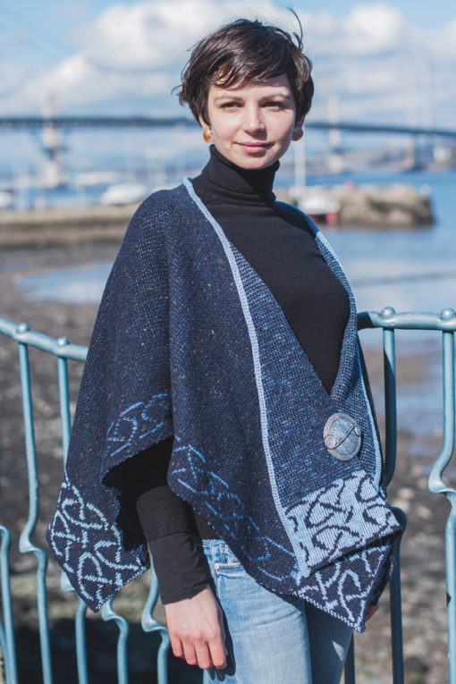 Front image of Woman wearing a blue color Celtic Stole with red bridge and river in background, by Bill baber clothing of Scotland. Available at www.realirish.com in the USA