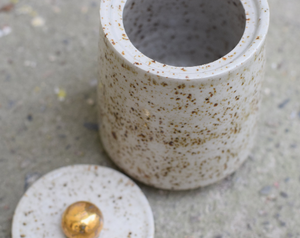 Speckled jar with gold handle.