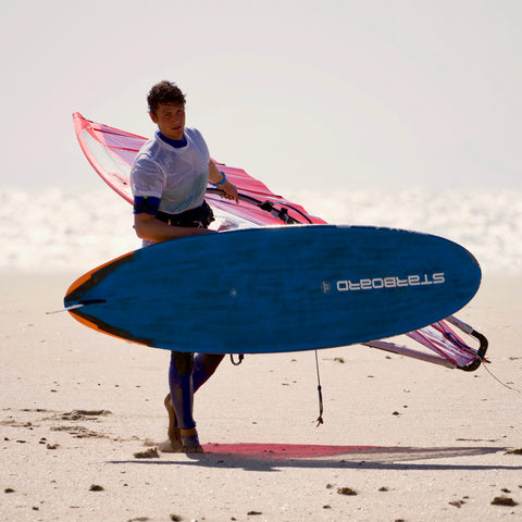 Julien Pockrandt JPag in Jibe Wear Windsurf Clothing carrying windsurf board