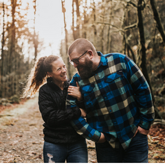 couple in a forest laughing