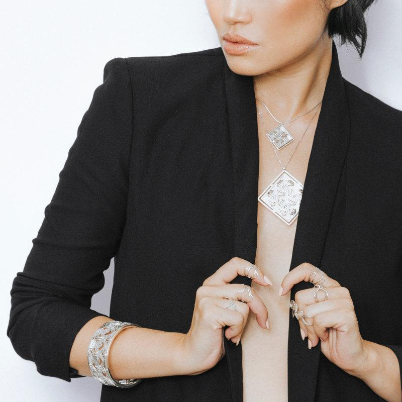 Model Wearing Custom Made Sterling Silver Pendants, Rings, and Bracelet