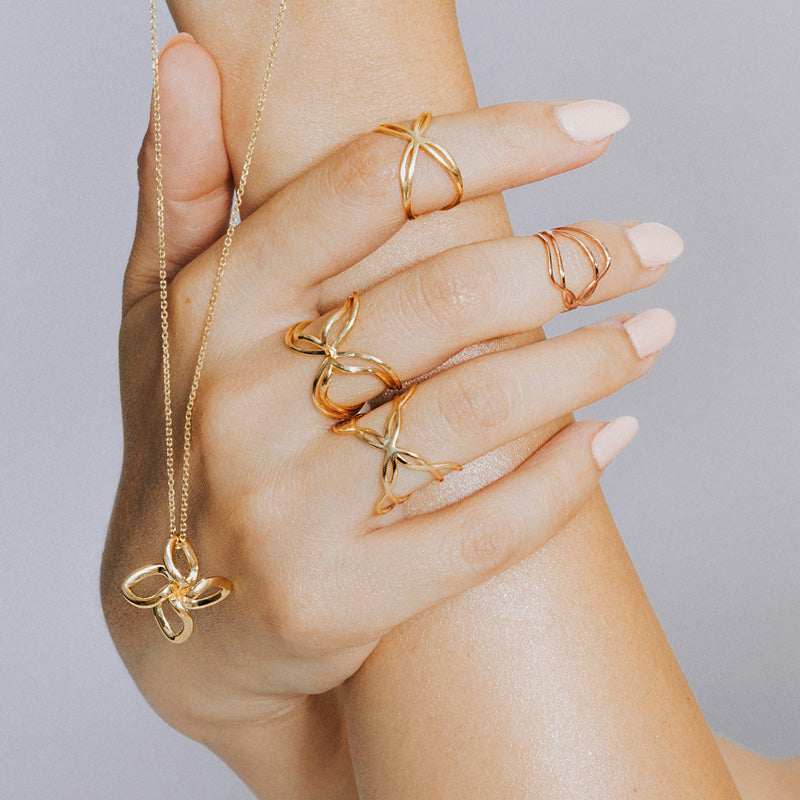 18K yellow gold 3D printed Wanderlust Butterfly Ring styled with other gold rings and pendant