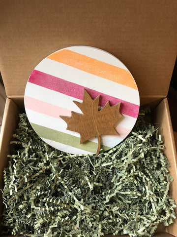 Circular multi striped sign with a maple leaf