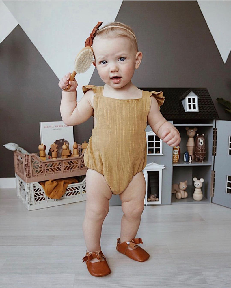 Little Ballerina vegan moccasins collection in brown on a toddler