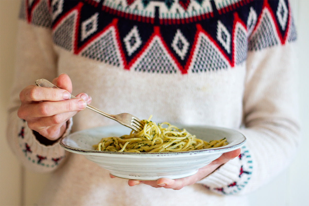 woman wearing a winter jumper holding a bowl of pasta and pesto