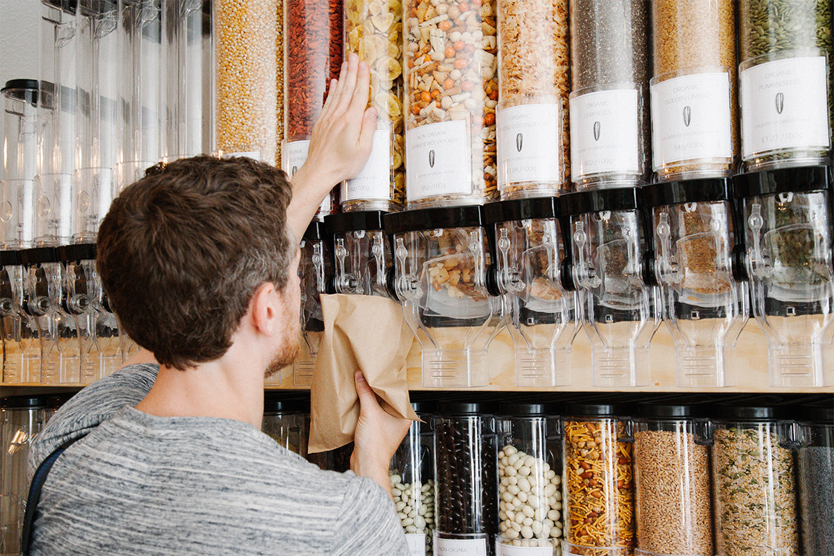 customer filling a container with dry goods at un_rap refill store in Falmouth, by Bell Rose Bunce