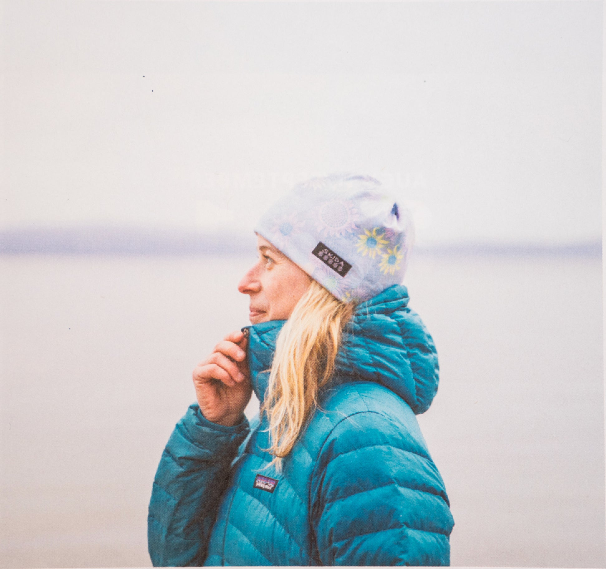 woman outdoors in winter jacket and Skida hat