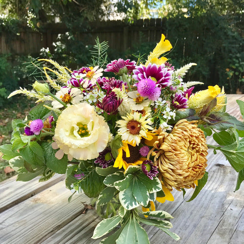 Medium bouquet in a fall gold, white, yellow, and purple. Flowers include lisianthus, calendula, mums, celosia, amaranth, and zinnias.