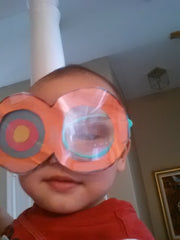 photo of baby with big paper glasses on