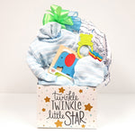 A cute baby gift box holding a knit outfit or sleeper, a receiving blanket, baby bib, teething rattle and classic baby puzzle for the new little star.