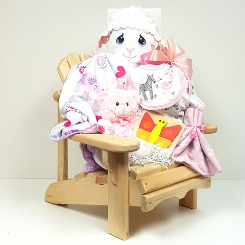 A baby gift basket consisting of a beautifully crafted muskoka chair filled with a plush blanket, Precious Moments hooded towel, onesie, bib and more.