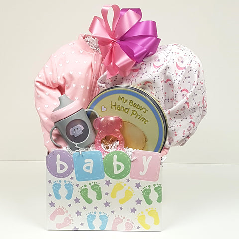 A molded handprint kit, a sleeper, receiving blanket, baby teether and baby's first sippy cup all nestled in a cute baby gift box.