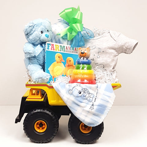A dump truck baby gift basket filled with a baby onesie, plush blanket, baby's first teddy,a board book and a classic stacker wooden toy.