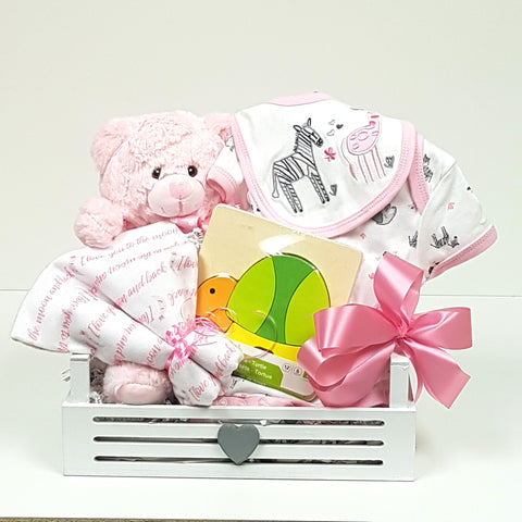 Baby's first teddy, a onesie, receiving blanket, classic wood puzzle and baby bib nestled with love in a cute wooden baby gift basket box.