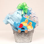 A pretty silver tin baby gift basket containing a onesie, receiving blanket, baby board book and a classic pull toy.