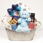 A beautiful silver tin baby gift basket brimming with treats for mom and dad, a mug, a plush baby blanket and teddy bear too.