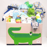 A toy box gift basket filled with blankets, outfits, hooded towel, Mama and baby plush, baby's first sippy cup, a keepsake timecapsule for baby's special firsts, baby's first book and so much more.