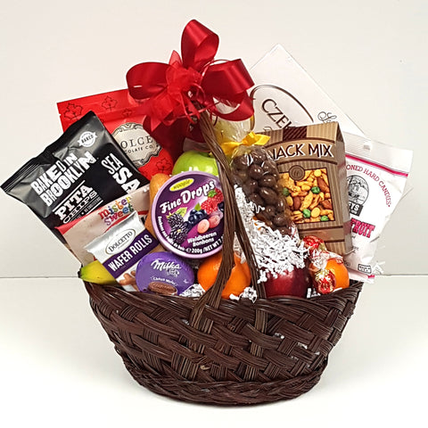 A gift basket containing a mix of fruit nestled in a generous collection of sweet and salty treats.