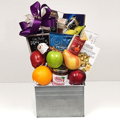 A  fruit gift basket holding a bountiful assortment of fruit, jam, cheese, crackers, nuts, chocolates and so much more.