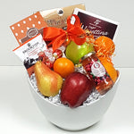 Cookies, specialty chocolates and some sparkling jelly too nicely arranged with some fruit in a beautiful ceramic fruit gift basket bowl.