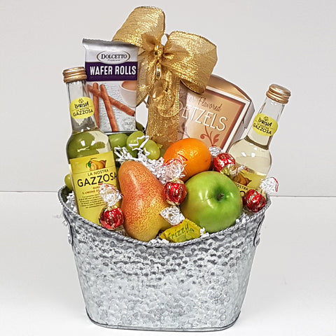 A silver fruit gift basket holding a bit of sweet, a bit of salty, some fruit and some refreshing sparkling water.