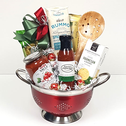 A classy red gourmet gift basket colander brimming with pastas, Italian pasta sauce, crackers, savoury shortbread, gourmet dipping sauce and a wooden pasta spoon.