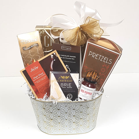 A beautiful white and gold tin gift basket filled with crackers and cheese, maple glazes smoked salmon, pretzels, red pepper jelly, cookies & chocolate too.