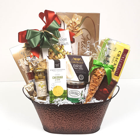 A gourmet gift basket with a chockful of chocolate, nuts, crackers, cheese, gourmet dip mix, nuts, red pepper jelly, savoury shortbread, pepperoni and more.