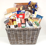 A large bold wicker hamper gift basket is overflowing with a cheese board, cheeses, gourmet sauces, Gazzosa sparkling water, chocolates, Hungarian Salami, nuts, crackers, cookies, Sea Change Smoked Salmon, mustards and lots more.