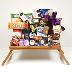 A breakfast tray gourmet gift basket overflowing with coffee, tea, pancake mix, handmade shortbread, jam, Royal Canadian wildflower honey, maple syrup, a pair of coffee mugs, sparkling apple cider and European chocolates to name a few.