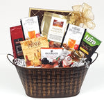 A gourmet gift basket consisting of coffee, spiced apple cider and tea along with some biscuits, chocolates, crackers and lovely Cider Keg sparkling jelly nestled in a pretty basket weave tin.