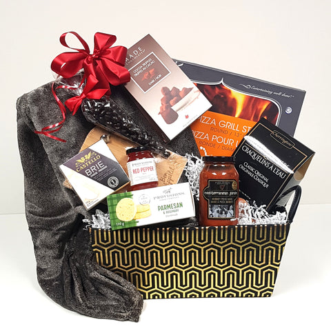 A warm cuddly blanket is nestled in a beautifully designed gourmet gift basket of black and gold along with a pizza stone, gourmet pizza sauce, crackers, and cheese, a mini cheese board, savoury shortbread, red pepper jelly and truffles and chocolates.