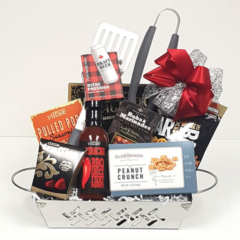 A beautiful stainless steel grill gift basket containing a set of BBQ utensils, BBQ sauce and seasonings, bar mix munchies, truffles and peanut crunch too.