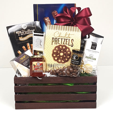 A crate gourmet gift basket loaded with chocolates, cookies, crackers, cheese, red pepper jelly, mustard and savoury shortbread too.