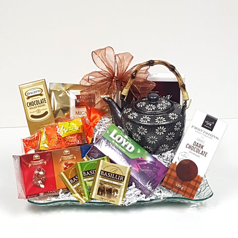 A beautiful glass tray gift basket adorned with a classic teapot and a variety of tea and biscuits to indulge in.