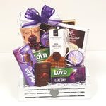 A pretty wood crate gift basket loaded with a birthday mug, cookies, chocolates and a variety of tea.